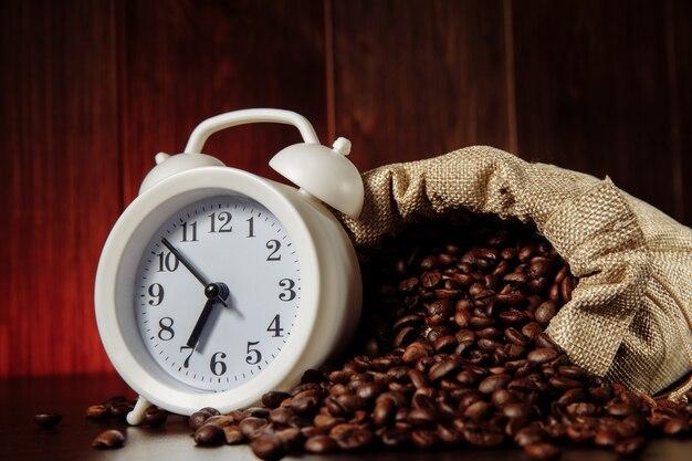 Biały budzik i ziarna kawy w zbliżeniu worka