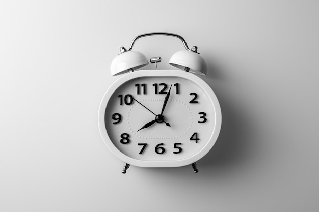 Biały budzik na białym biurku. koncepcja pomysłów na myślenie i synchronizację.