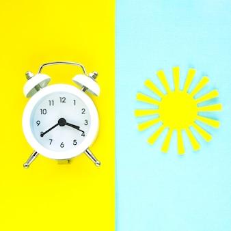 Biały budzik na jasnym żółtym tle i papierowe słońce na niebieskim tle. koncepcja lato.