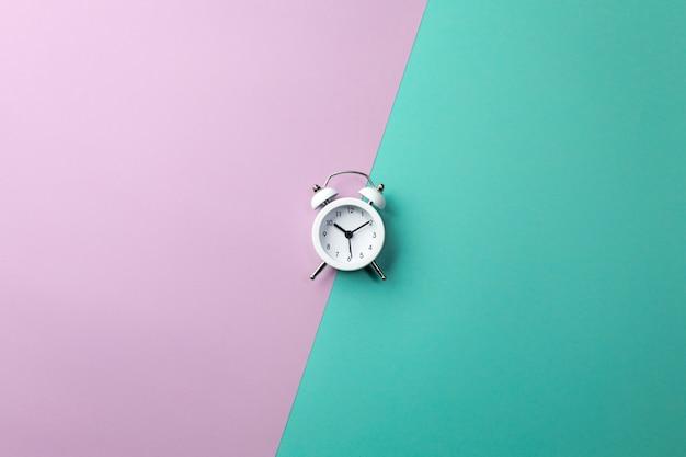 Biały budzik na kolorowym. koncepcja w minimalistycznym stylu