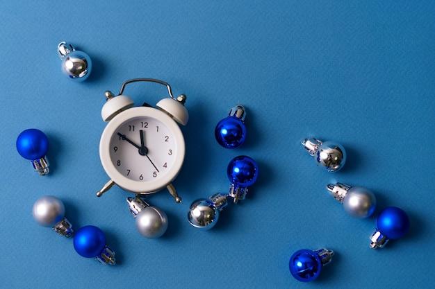 Biały budzik na niebieskim stole z bombkami. koncepcja dekoracji świątecznych