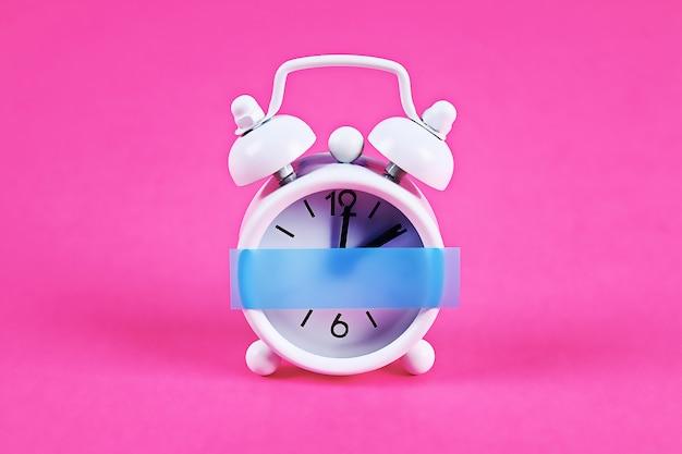 Biały budzik na różowym pastelowym kolorze