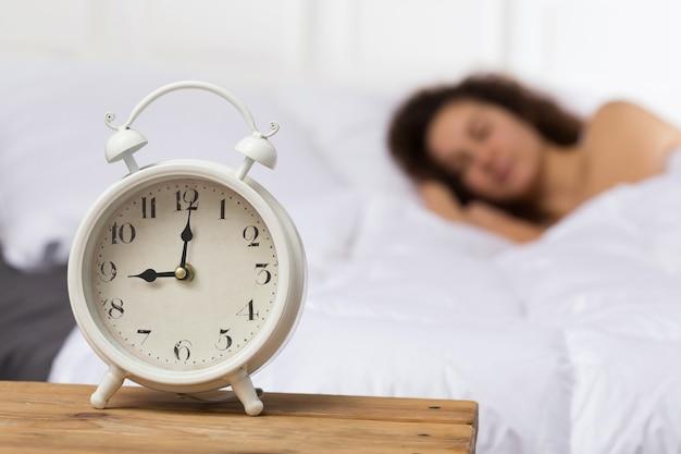 Biały budzik na tle śpiącej dziewczyny. dziewczyna na łóżku jest zamazana. leży na prawym boku. godzina 9.