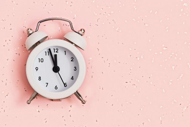Biały budzik pokazuje godzinę dwunastą na różowym papierze pokrytym cekinami