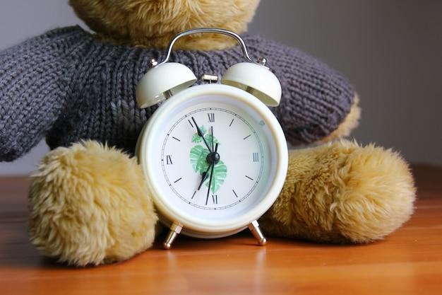 Biały budzik przed zabawką z niedźwiedziem brunatnym