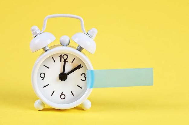 Biały budzik. pusta karteczka na zegarze. kopia miejsca. minimalna koncepcja.