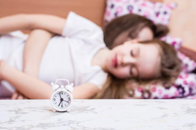 Biały budzik stoi na stole na tle dwóch śpiących dziewczyn w łóżku