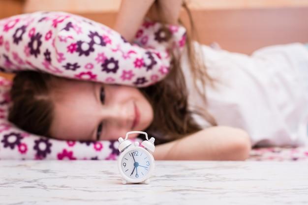 Biały budzik stoi na stole na tle dziewczyny zakrywającej uszy poduszkami