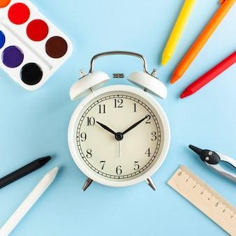 Biały budzik w otoczeniu kolorowych długopisów i innych przyborów szkolnych. koncepcja plastyczna początku roku szkolnego