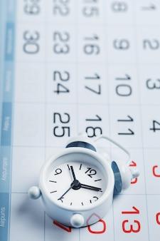 Biały budzik znajduje się w kalendarzu z datami