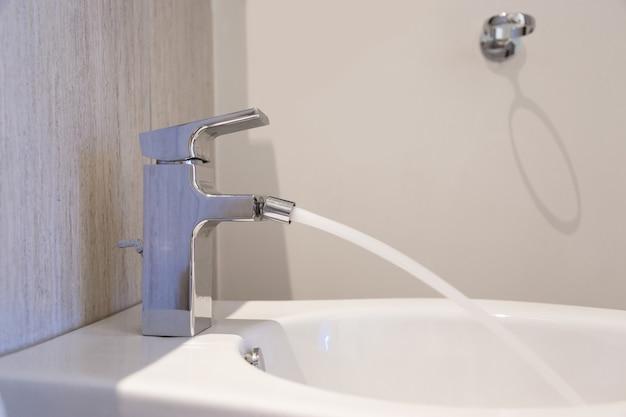 Biały ceramiczny bidet w nowoczesnej łazience z otwartą baterią