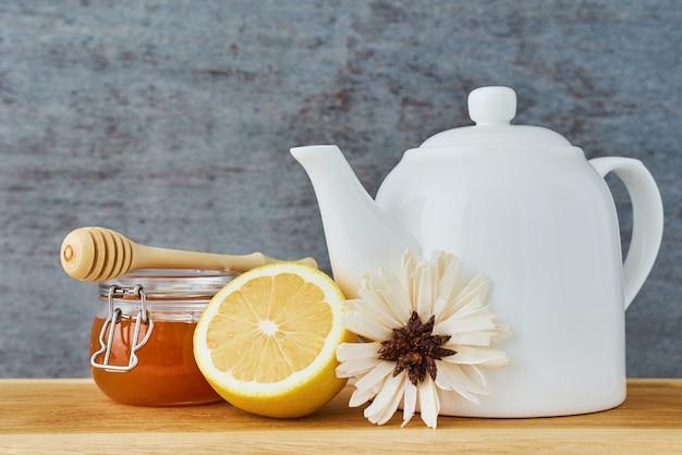Biały ceramiczny czajniczek, miód lemonnd w szklanym słoju z bliska