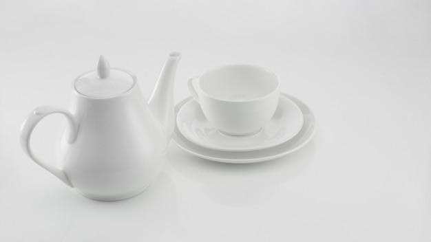 Biały ceramiczny czajniczek z filiżanką na jasnym tle