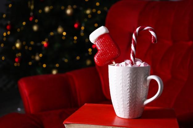 Biały ceramiczny kubek z cukierkami świątecznymi na choince. kompozycja świąteczna.