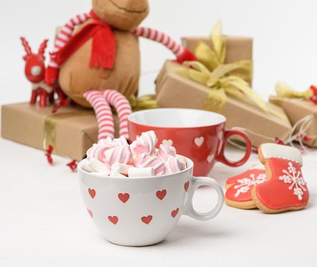 Biały ceramiczny kubek z kakao i piankami, za pudełkiem prezentowym i świąteczną zabawką