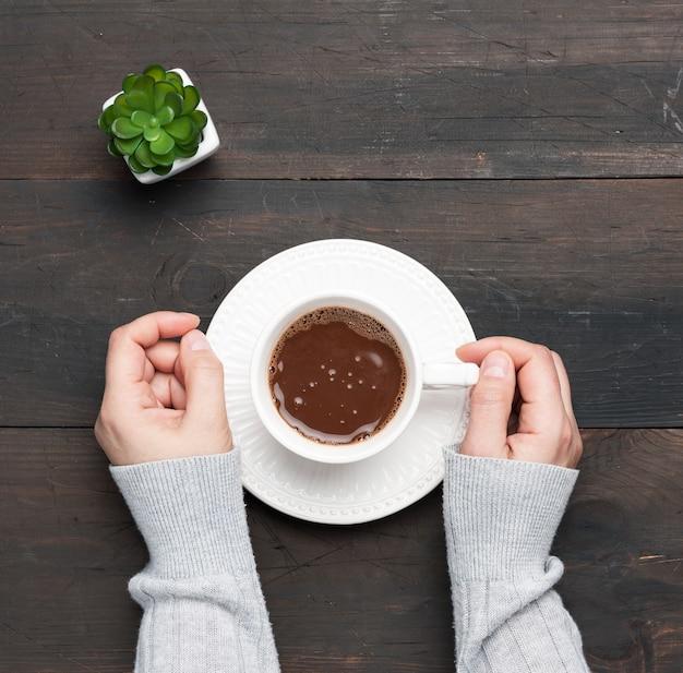 Biały ceramiczny kubek z kawą i dwie kobiece dłonie na brązowym stole, widok z góry