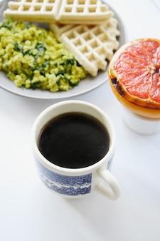 Biały ceramiczny kubek z kawą i zdrowym jedzeniem