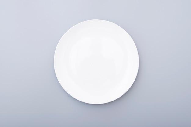 Biały ceramiczny talerz na popielatym stole, widok z góry białego naczynia. okrągły talerz, miska.