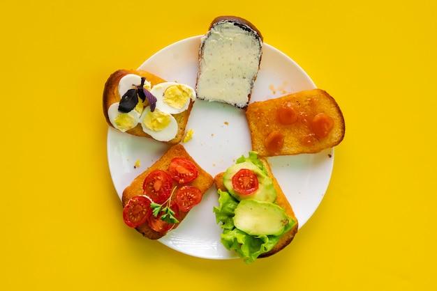 Biały ceramiczny talerz z zestawem kanapek z awokado, jajkiem, masłem, pomidorem i dżemem