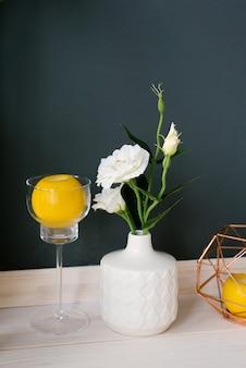 Biały ceramiczny wazon ze sztucznym białym kwiatem eustoma i cytryną w kieliszku na nóżce