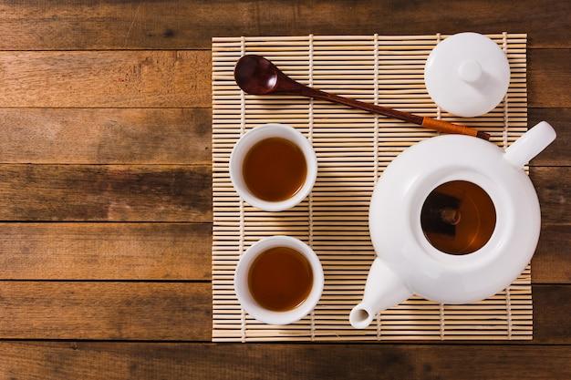 Biały chiński herbaciany ustawiający na drewnianym stole, odgórny widok