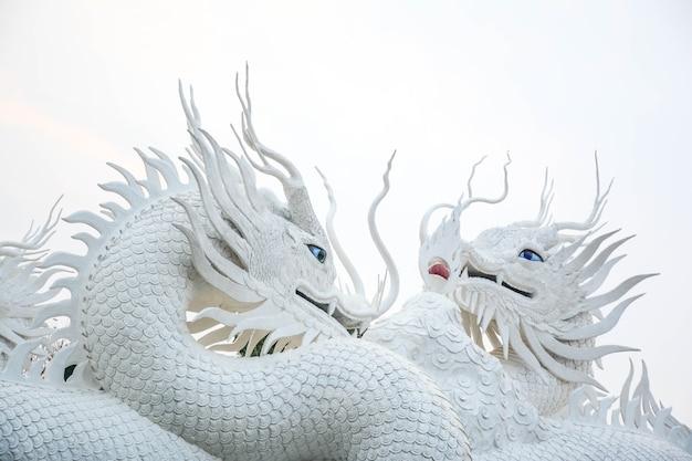 Biały chiński smok ozdobiony na tle chińskiej rzeźby smoka