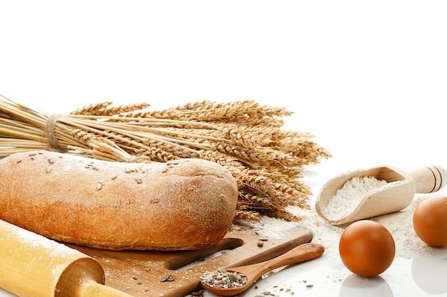 Biały chleb i naczynie do gotowania na białym tle na białym stole