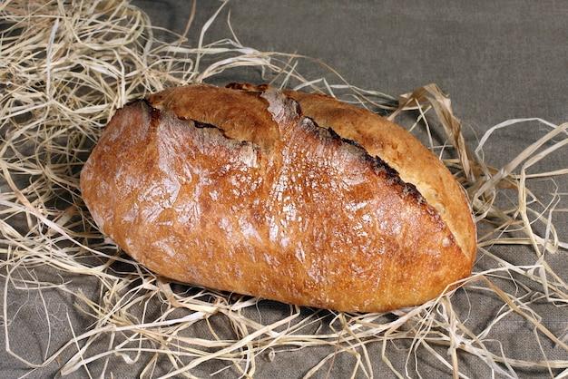 Biały chleb leżący w słomie na szarym lnianym obrusie
