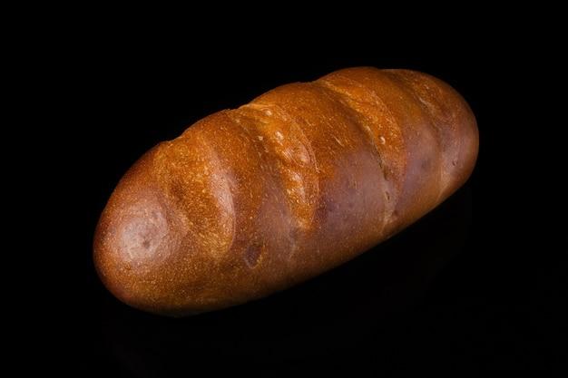 Biały chleb na czarnym tle.bochenek
