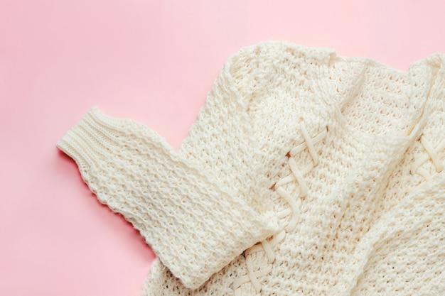 Biały, ciepły damski sweter z dzianiny na delikatnym różowym tle
