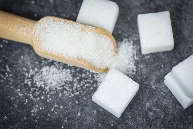 Biały cukier i cukrowi sześciany na drewnianej miarce z ciemnym tłem