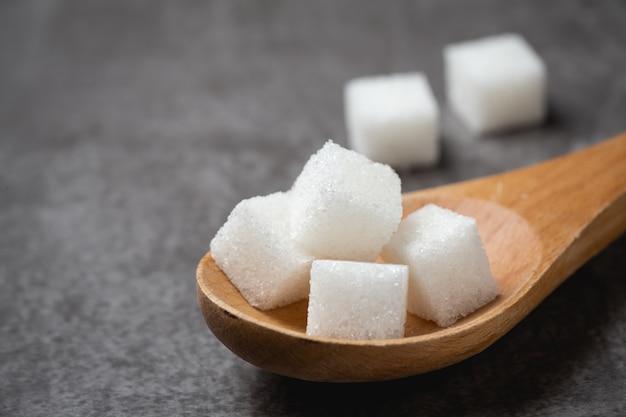 Biały cukrowy sześcian w drewnianej łyżce na stole.