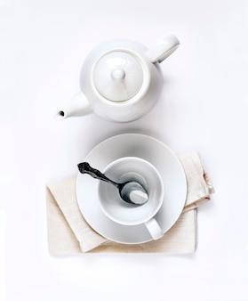 Biały czajniczek i pusta filiżanka z łyżką na białym tle płaski widok z góry