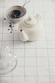 Biały czajniczek, kubki i sitko na obrusie w kratkę