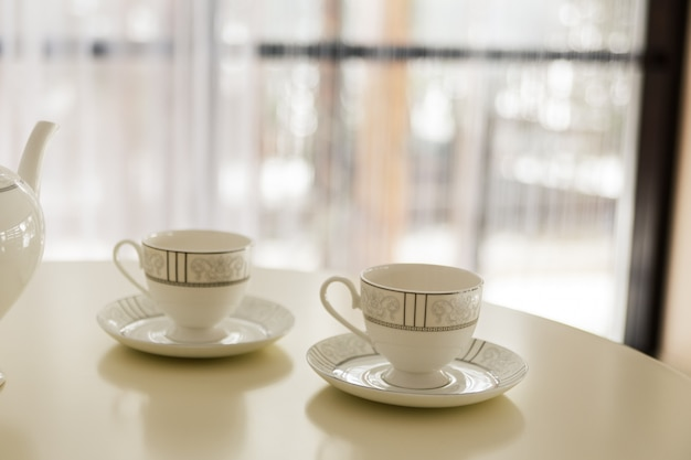 Biały czajnik i dwie filiżanki do herbaty na stole.