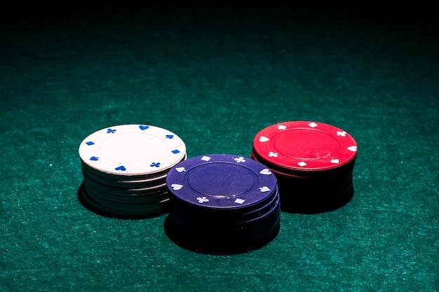 Biały; czerwony i niebieski stos żetonów kasyna na zielonym stole pokerowym