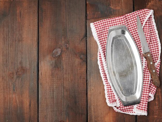 Biały czerwony ręcznik kuchenny w kratkę, żelazny talerz i ostry nóż vintage