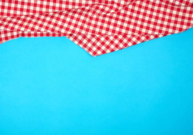 Biały czerwony w kratkę kuchenny ręcznik na błękitnym tle, jaskrawy pykniczny tło