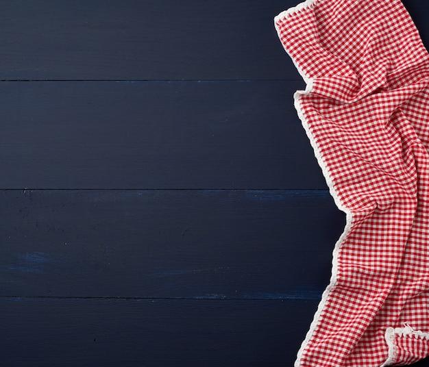 Biały czerwony w kratkę ręcznik kuchenny na niebieskim drewnianym