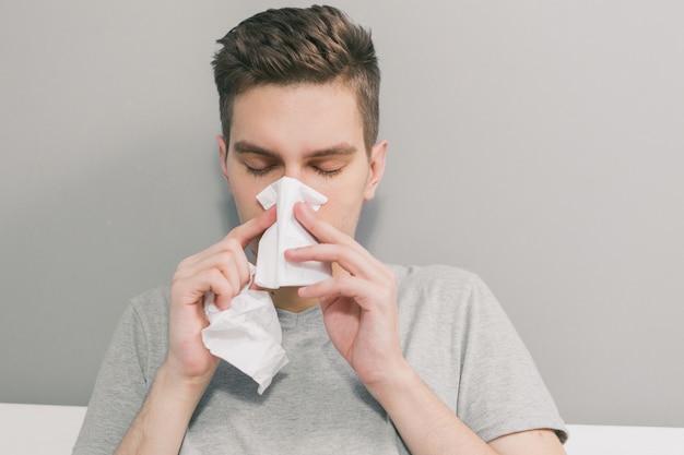 Biały człowiek zachoruje i wydmuchuje nos w białą serwetkę