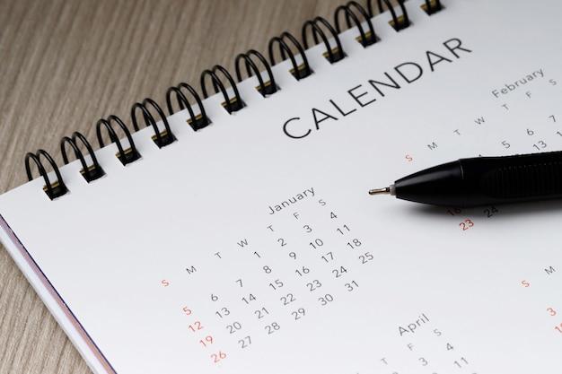 Biały czysty kalendarz i długopis na tle drewna z miejsca na kopię