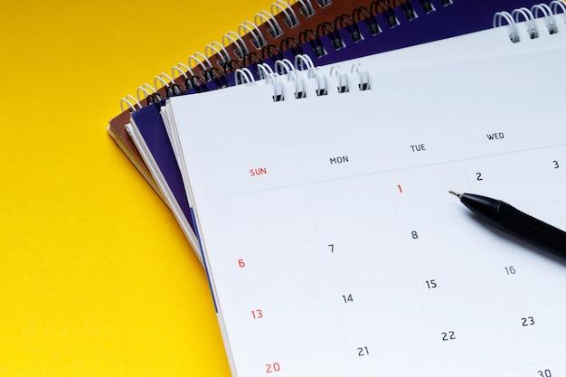 Biały czysty kalendarz i długopis na żółtym tle z miejsca na kopię