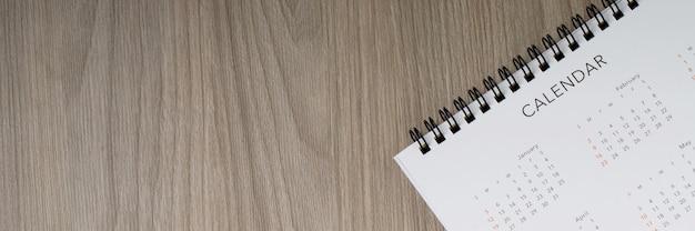 Biały czysty kalendarz na tle drewna z miejsca na kopię