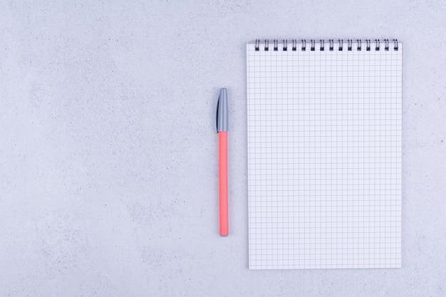 Biały czysty papier w kratkę z długopisem na szarej powierzchni