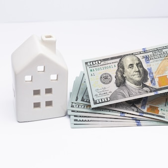 Biały dom z banknotami dolara gotówkowego w rękach jako symbol kredytu bankowego zaciągniętego jako pożyczka