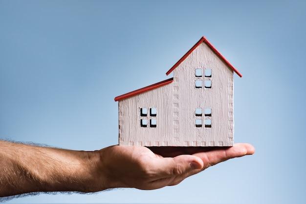 Biały dom z drewna na męskiej dłoni. koncepcja mieszkaniowa