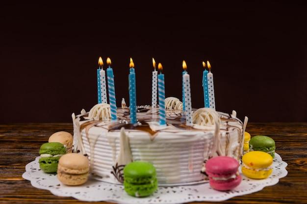 Biały domowy tort urodzinowy z dużą ilością płonących świec w pobliżu różnych kolorowych makaroników, na drewnianym biurku