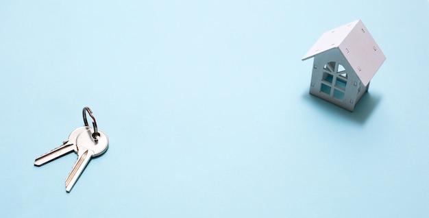 Biały drewniany dom symbol i klucze na niebiesko