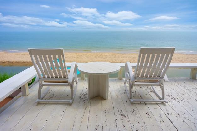 Biały drewniany plażowy krzesło blisko morza w lecie.