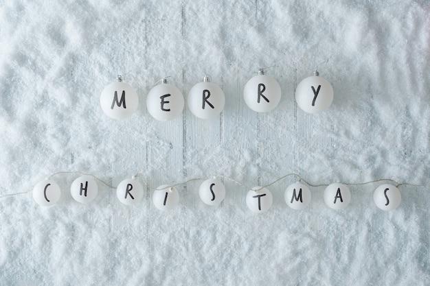 Biały drewniany stół z dekoracją w kształcie kulek ze śniegu i świateł. zimowy widok z góry wesołych świąt. minimalne płaskie ułożenie.